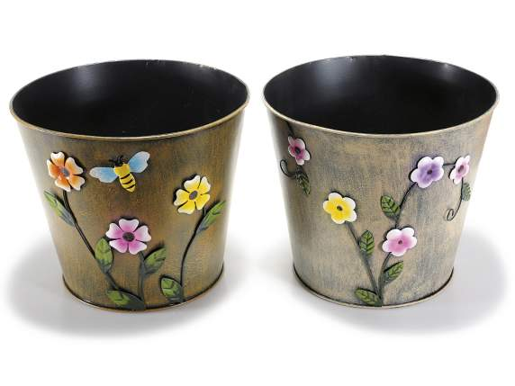 Metal flowerpot cover with flower decorations affixed